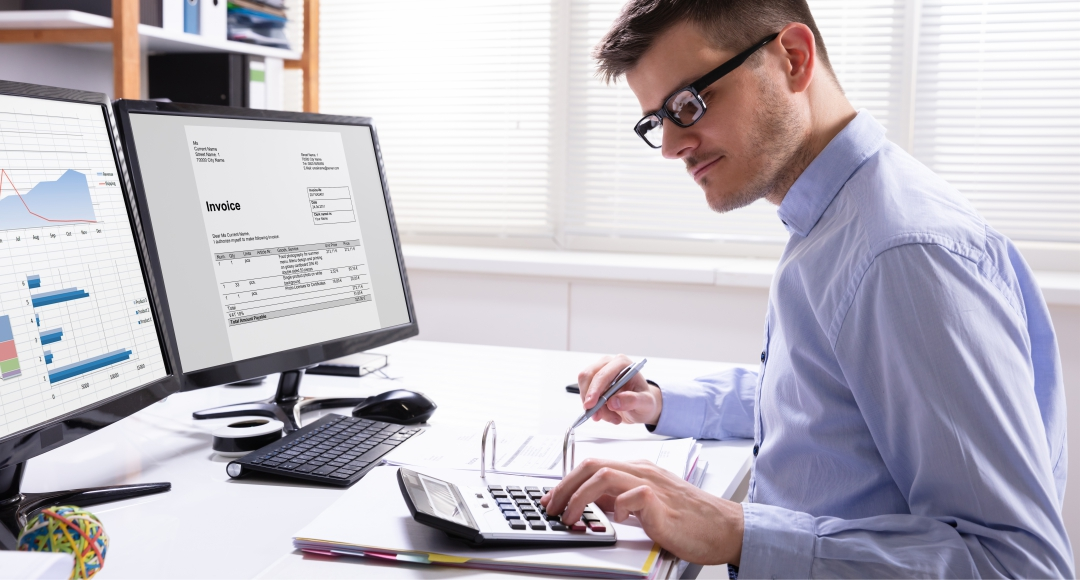 Accountant by computer working on some figures